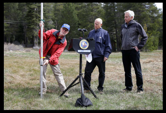 Governor Jerry Brown looks on as last April's snow survey is conducted on barren ground along Highway 50, near Echo Summit.