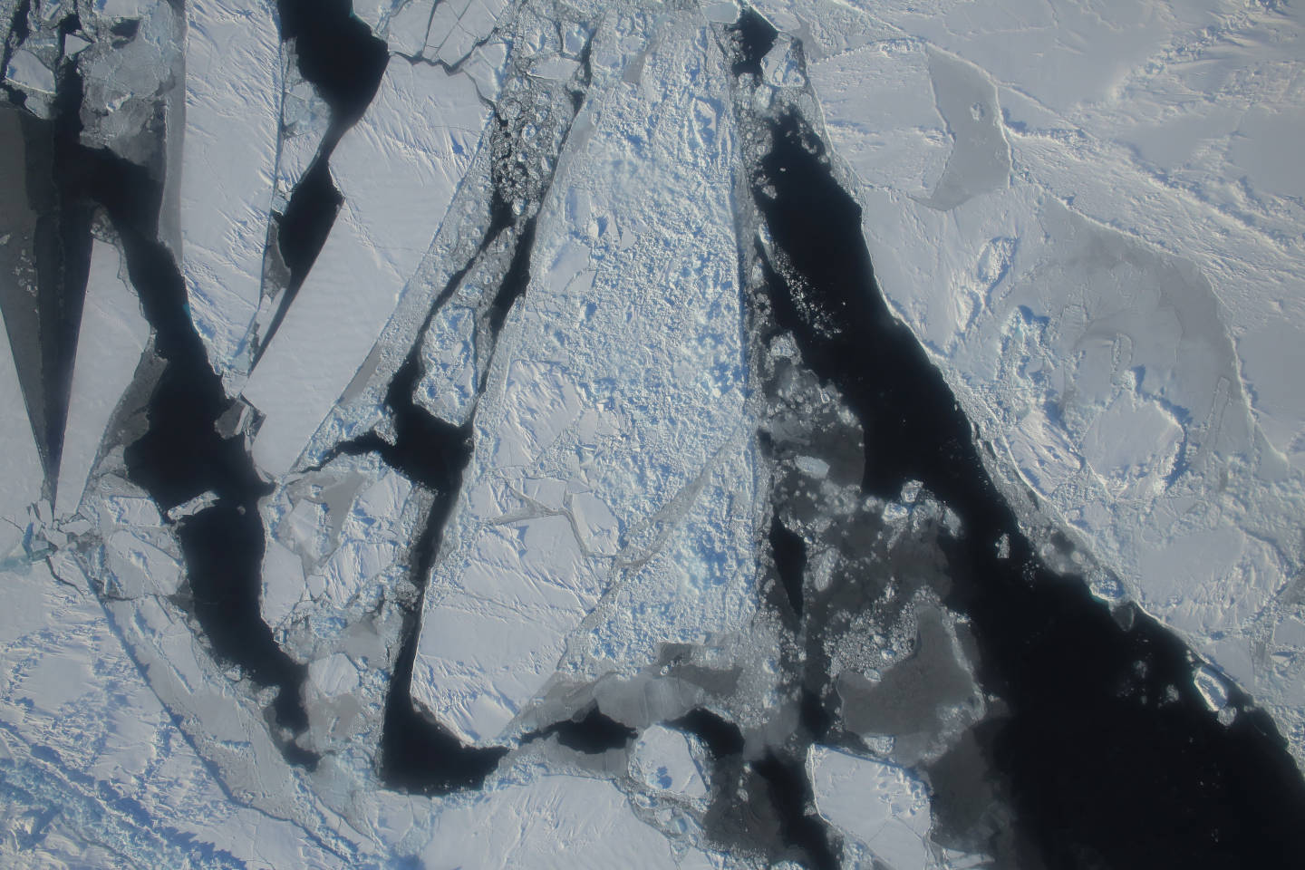 This photograph from a March 27, 2015 NASA IceBridge flight shows a mixture of deformed, snow-covered, first-year sea ice floes, interspersed by open-water leads, brash ice and thin, snow-free nilas and young sea ice over the East Beaufort Sea. Nilas are thin sheets of smooth, level ice less than 10 centimeters (4 inches) thick and appear darkest when thin.  NASA/Operation Ice Bridge.