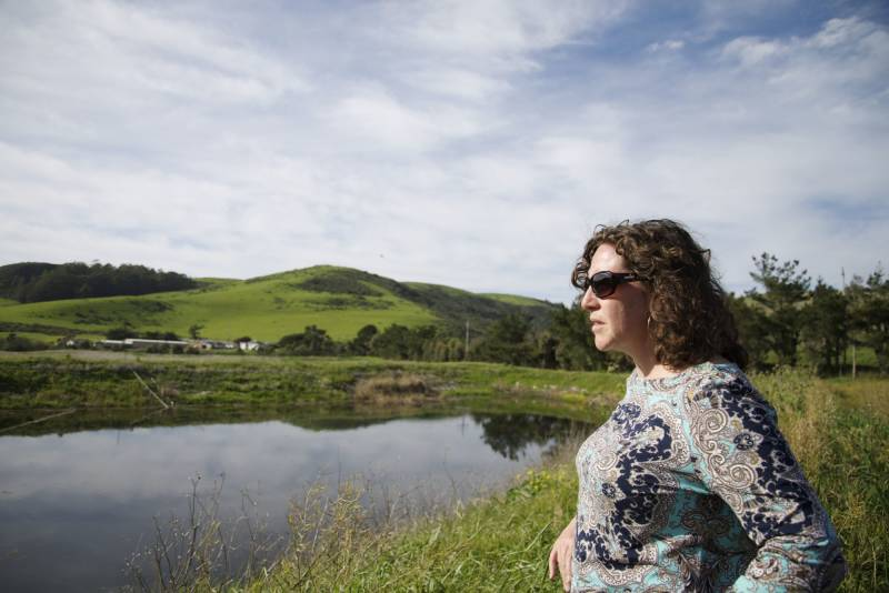 Kellyx Nelson, executive director of San Mateo County Resource Conservation District, stands next to a retention pond on land managed by flower grower Dave Repetto in San Mateo County, California.