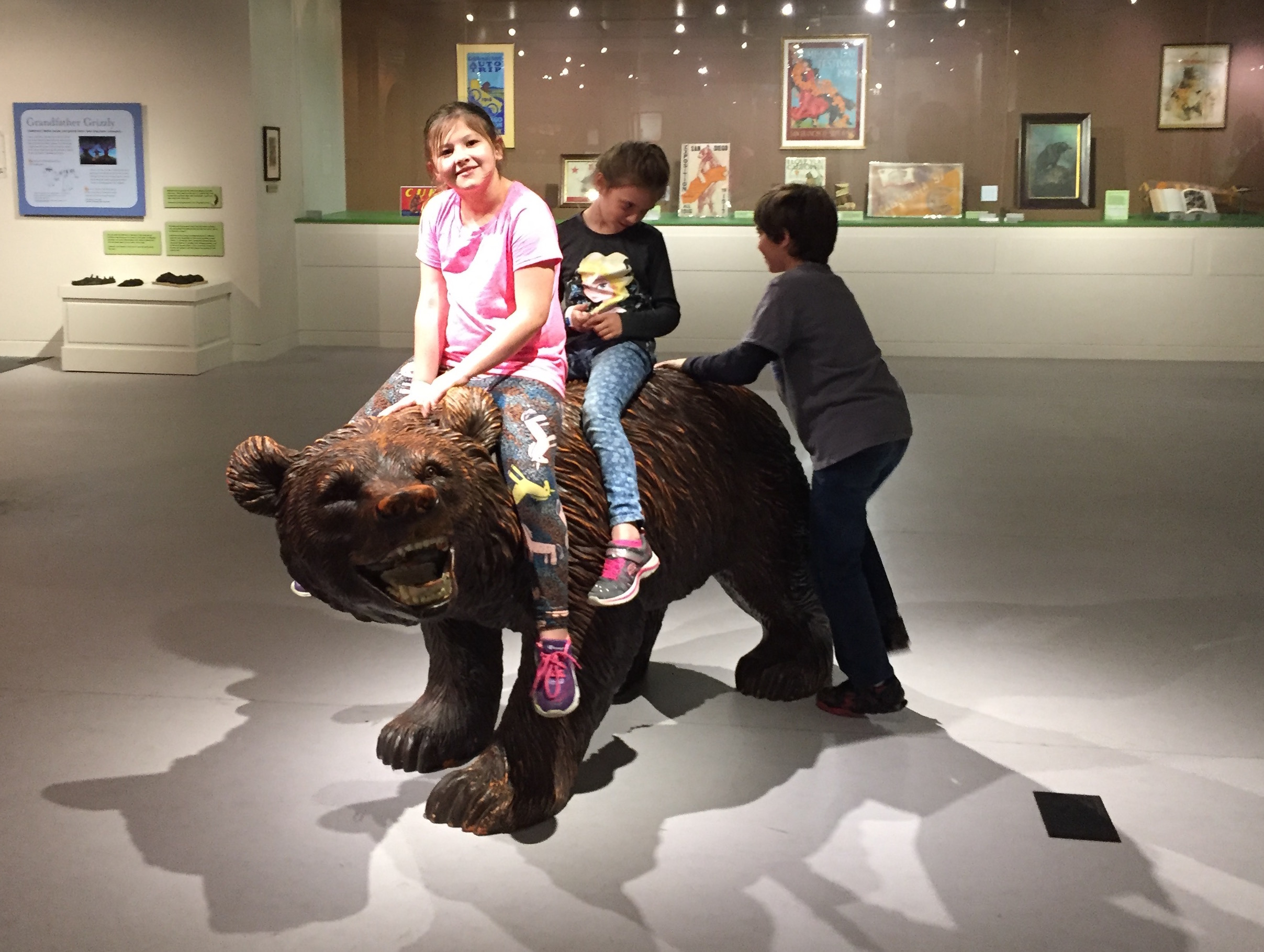 Kids play on a grizzly bear sculpture at the California Museum in Sacramento.