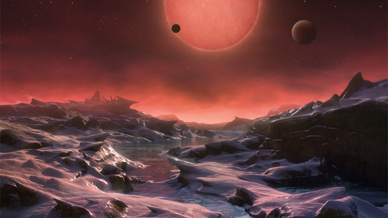 Artist depiction of the ultra-cool star TRAPPIST-1 and two of its recently discovered planets, seen from a third.