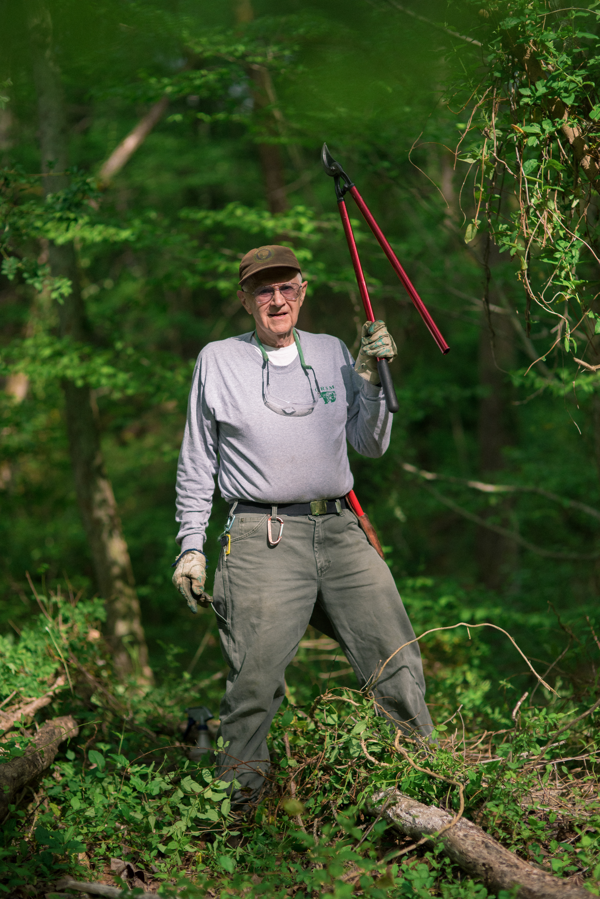 """Paul """"Doc"""" Hadala, a volunteer at Great Smoky Mountains National Park, works to eliminate invasive plant species from a section of forest."""