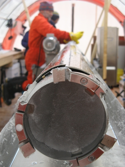 An ice core still sits inside a drill.