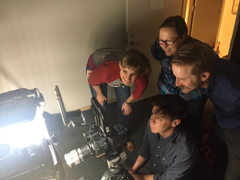 Four people watching a camera film an aquarium.