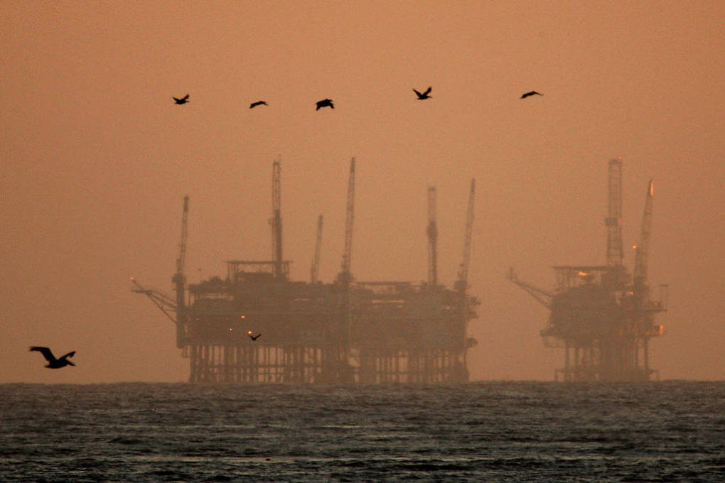 California brown pelicans fly near offshore oil rigs after sunset on July 21, 2009, near Santa Barbara, California.  David McNew/Getty Images