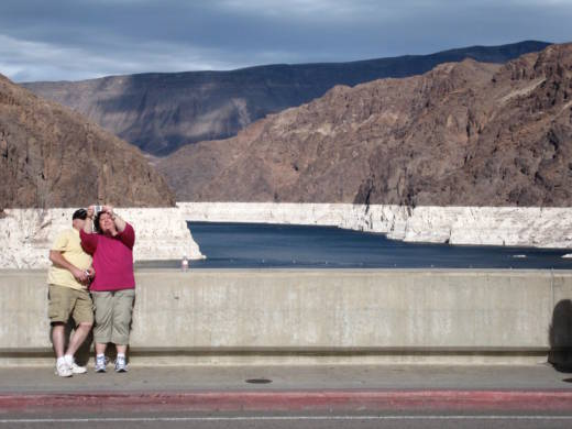 "Tourists take a selfie on the lip of Hoover Dam, overlooking Lake Mead, in the fall of 2009. The gray ""bathtub ring"" around the shoreline, shows how the water level had dropped. In 2016 it reached its lowest level since the huge reservoir was filled in the 1930s."