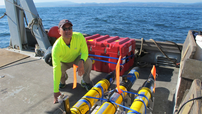 NASA/JPL's Steve Chien with some of the submarine drones being tested in Monterey Bay as autonomous ocean exploring robots.