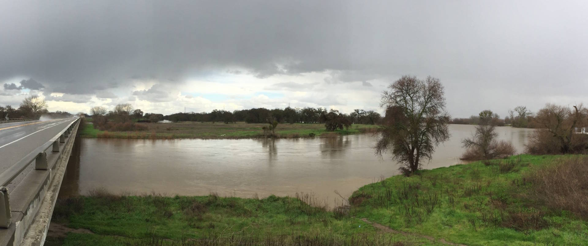 The San Joaquin River, which often runs dry before reaching its mouth, spreads out along Hwy 132 west of Modesto, after weekend storms. Craig Miller/KQED