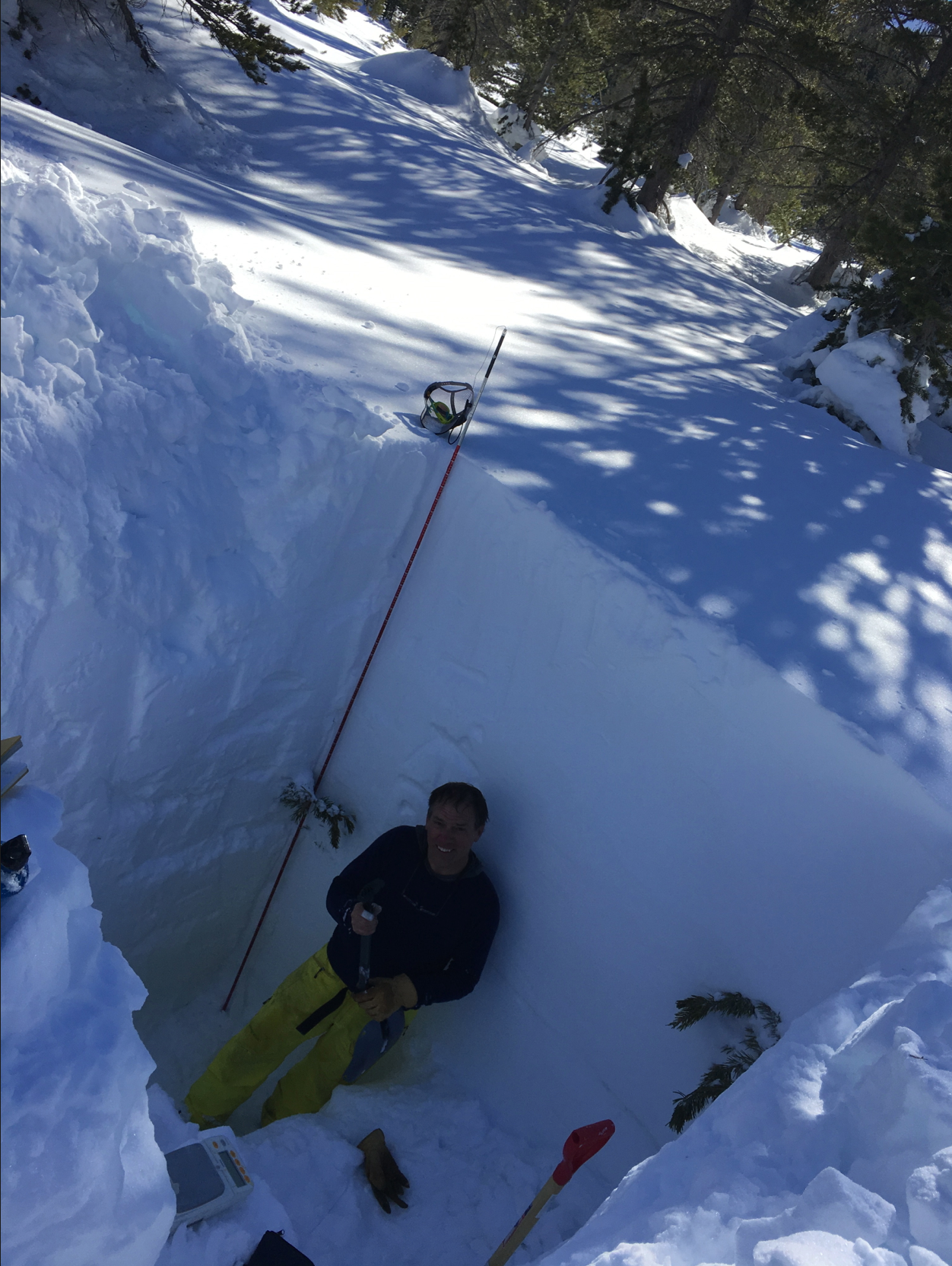 Snow hydrologist Tom Painter takes a break after digging out a snow pit, to measure density and other parameters.