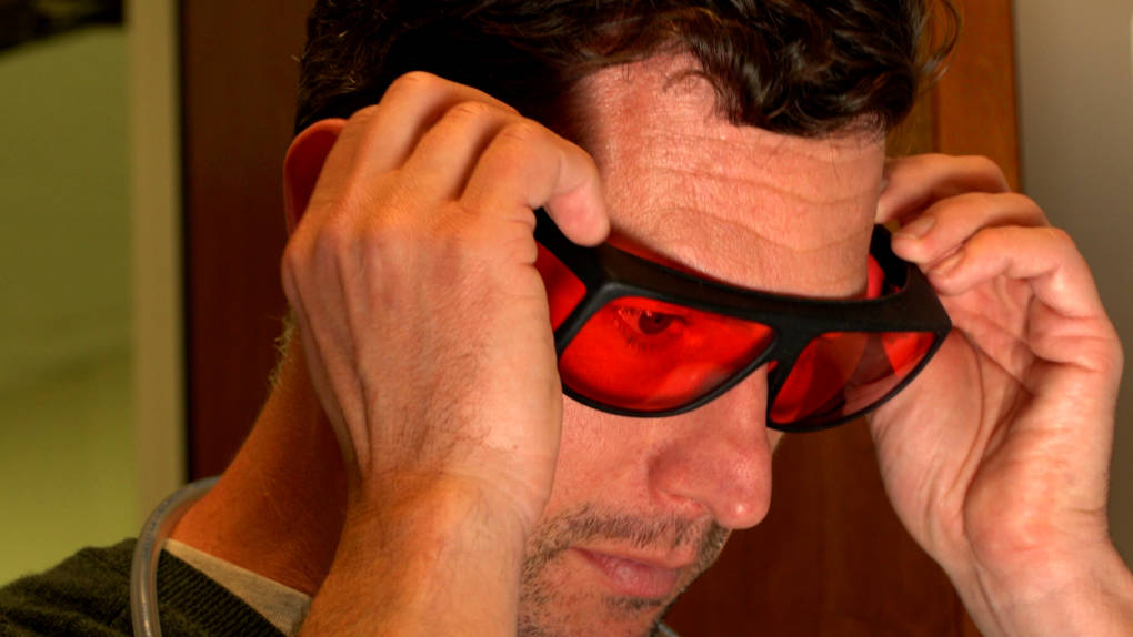 At Caltech, neuroscientist Eric Hoopfer puts on special glasses to protect his eyes from the red light he will flash on his research fruit flies.