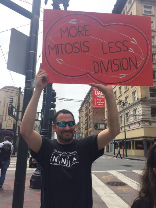 "A man holds a sign in Downtown San Francisco that says ""More mitosis less division."""