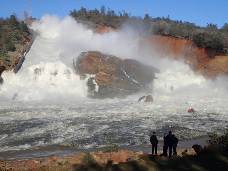 A Cal Fire team watches water surge down and around the collapsed main spillway at Oroville Dam on February 11.