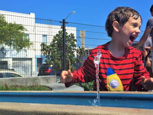 West Lord, 4, of San Francisco, delights in a new water fountain at the opening of In Chan Kaajal Park on June 23.