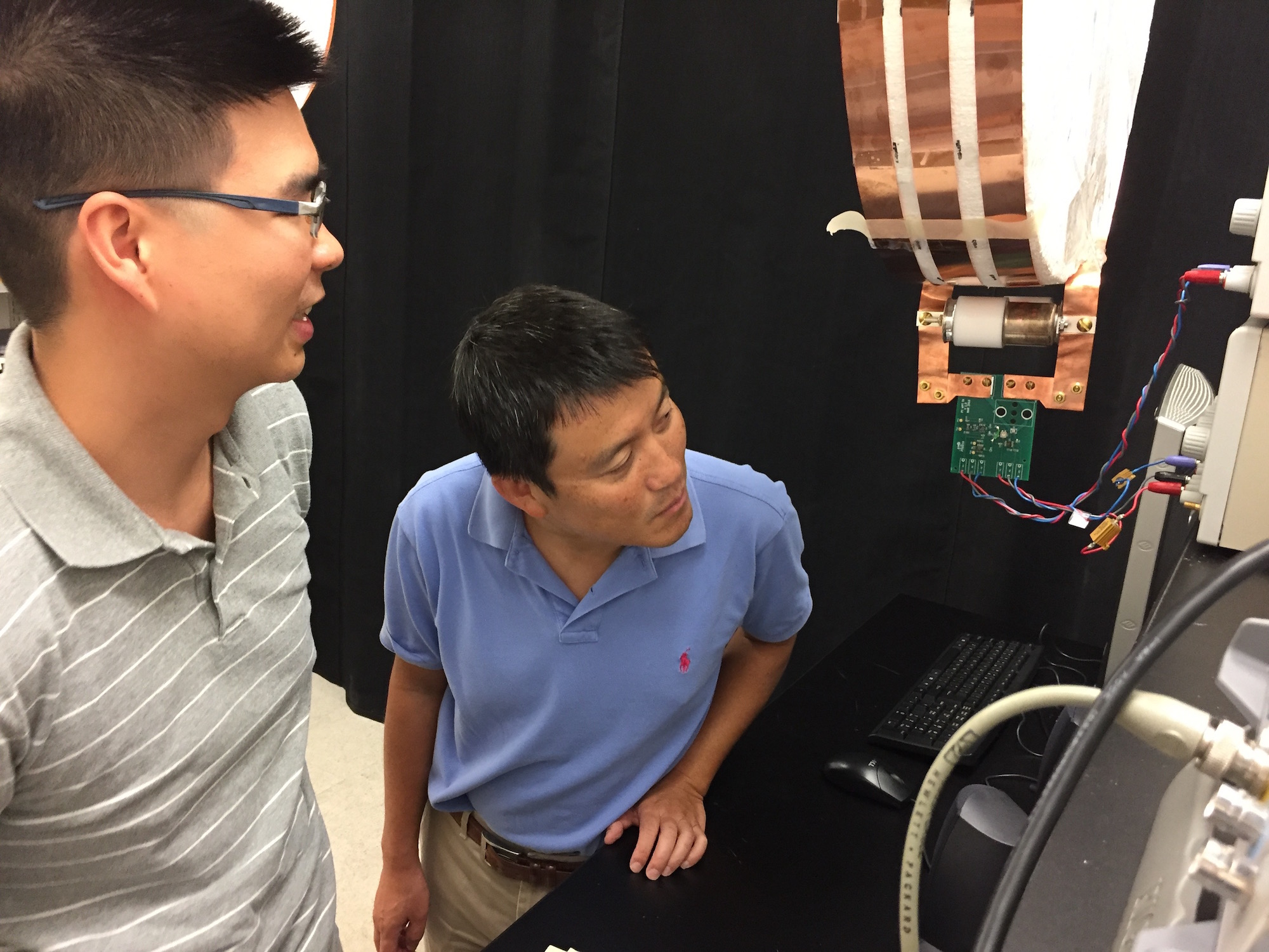 Electrical engineers Sid Assawaworrarit (left) and Shanhui Fan examine their demonstration apparatus for dynamic charging in their lab at Stanford.