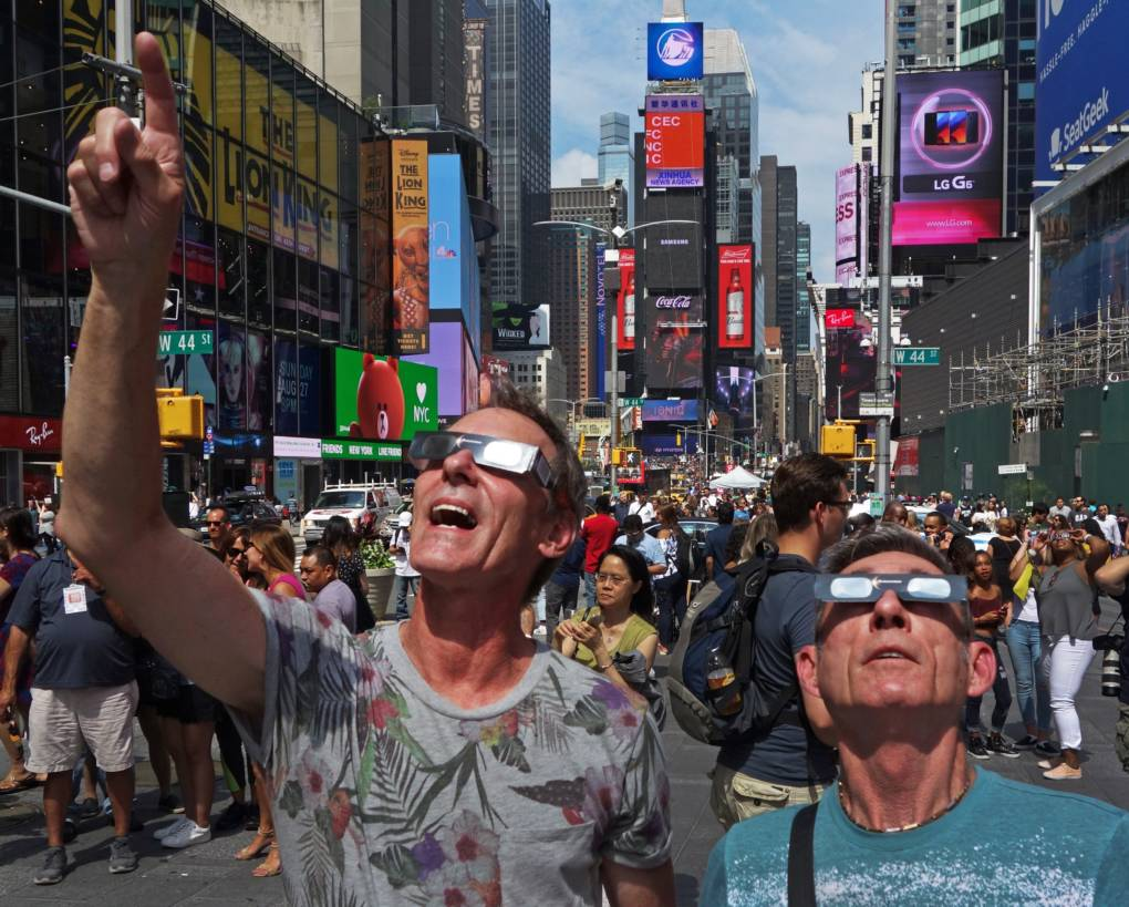 Thousands flocked to Times Square in New York City to view the partial eclipse. Emotional sky-gazers stood transfixed across North America Monday as the Sun vanished behind the Moon in a rare total eclipse that swept the continent coast-to-coast for the first time in nearly a century.