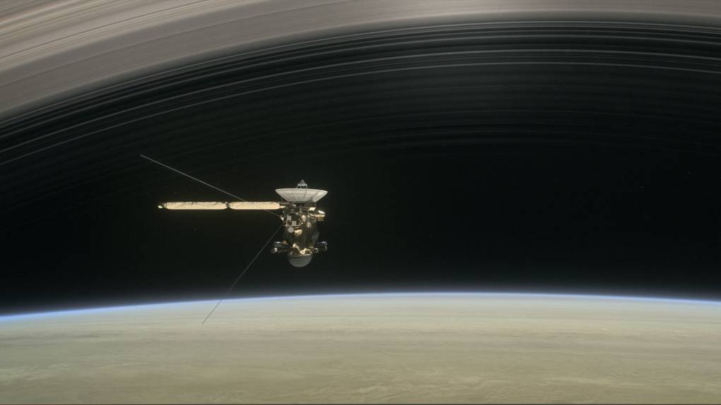 Artist concept of Cassini flying over Saturn's cloud tops and under its iconic rings.