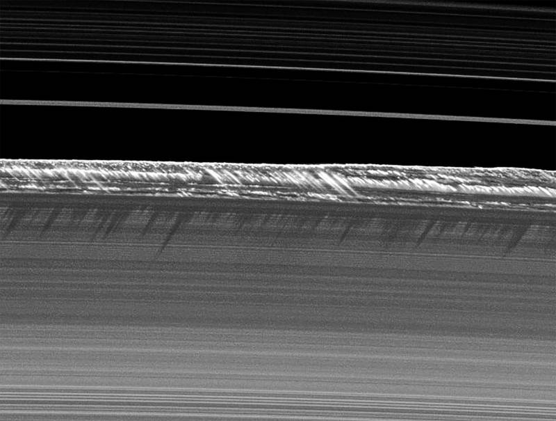 "Vertical structures in Saturn's rings rising up to a mile above the ring plane, kicked up by gravitational disturbance of a tiny ""moonlet"" orbiting within the rings."