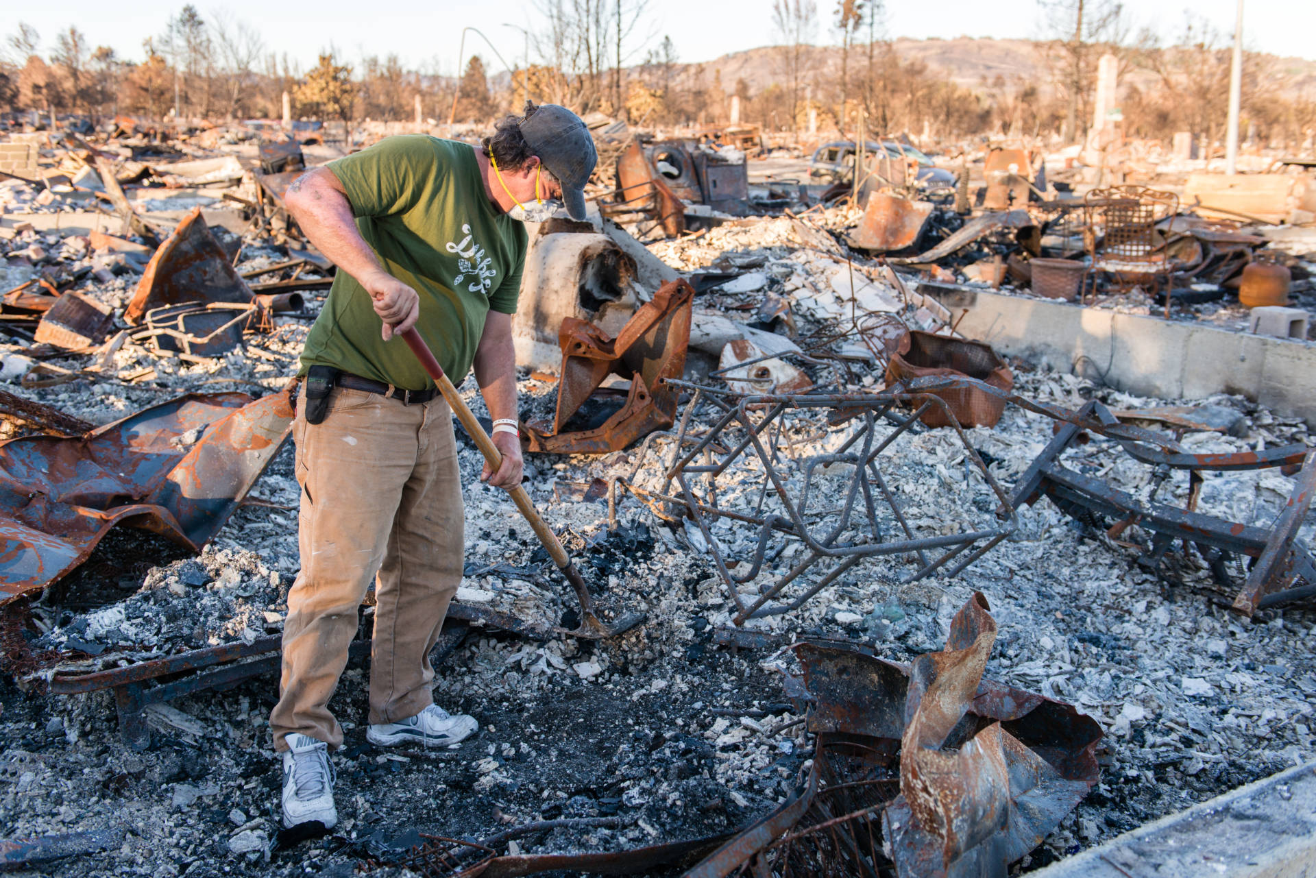 """Ed Corn wears a mask as he sifts through the ashes of the home he shared with his paraplegic roommate in Santa Rosa's Coffey Park neighborhood. """"I can definitely taste the toxins in my throat and the back of my tongue,"""" he said.   Heidi de Marco/KHN"""