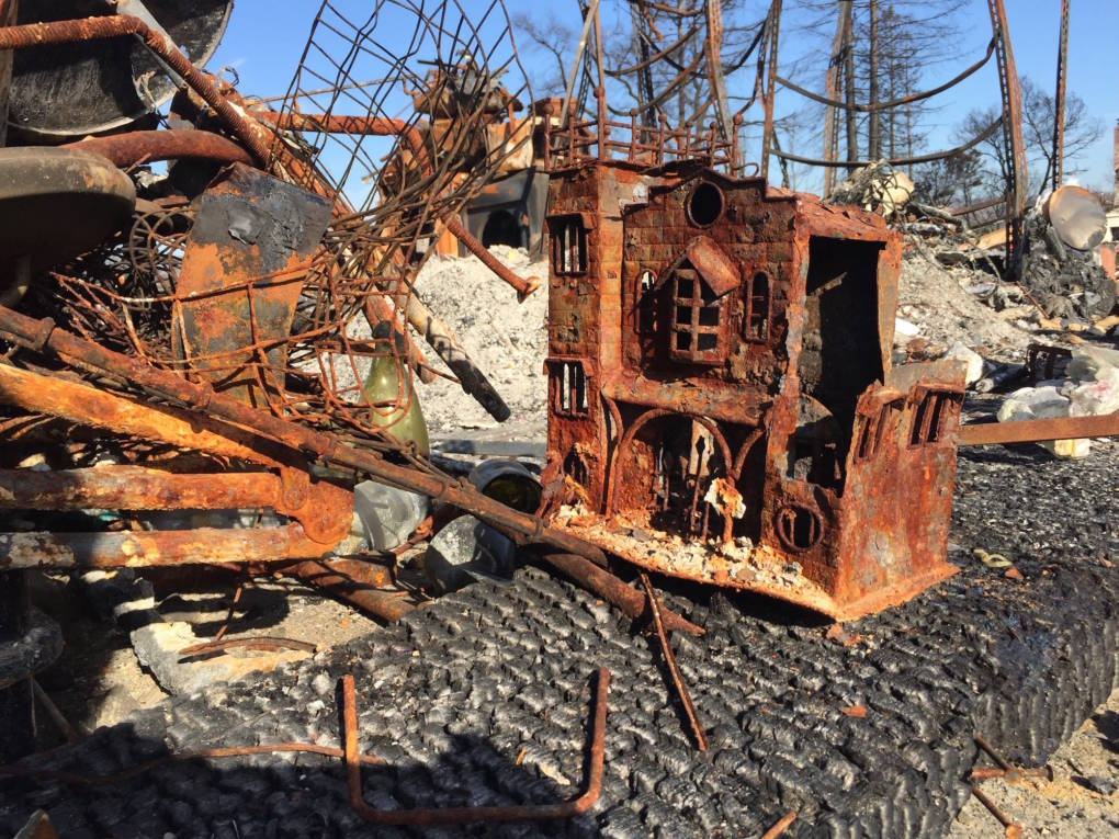 Dollhouse amid burned ruins.