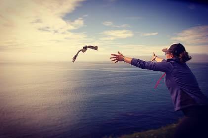 A woman releases a bird over the ocean
