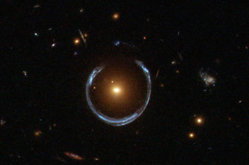 "A visible-light image of a gravitational lens captured by the Hubble Space Telescope. The central galaxy, LRG 3-757, is serving as a gravitational lens producing a distorted ""ring"" image of a more distant blue galaxy, positioned behind."