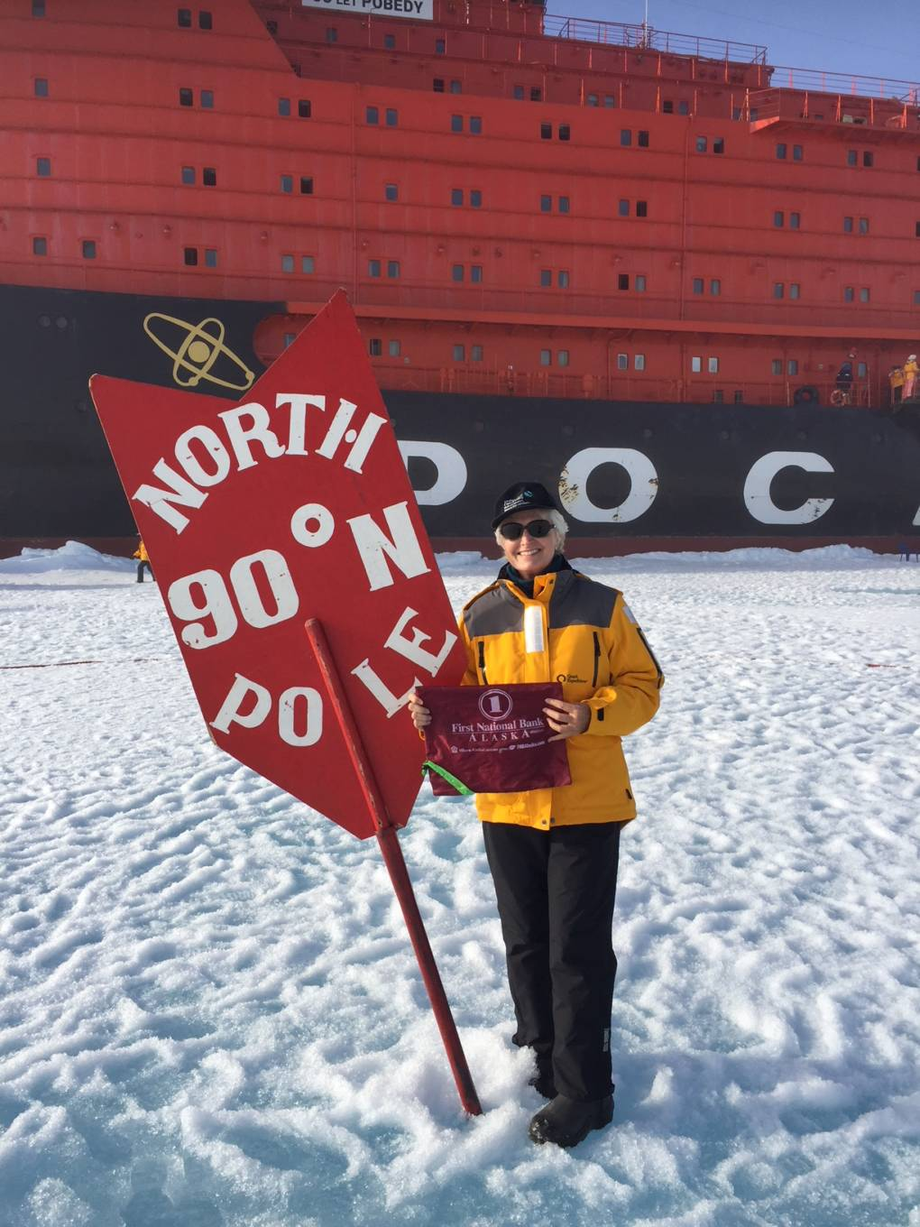 A woman stands next to a sign reading 'North Pole'.