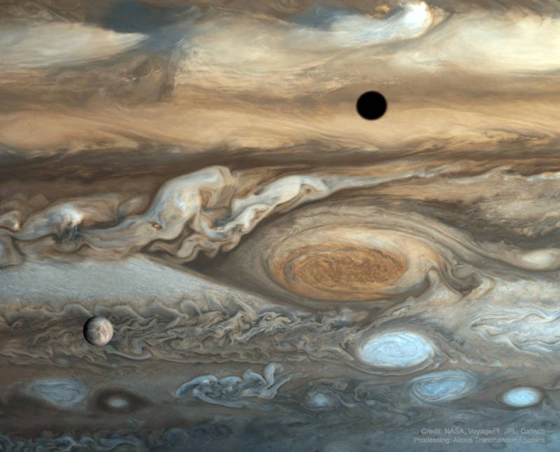 "Image of Jupiter and its famous ""Great Red Spot,"" with the moon Europa set in the foreground. The dark circle in the upper right is the shadow of the moon Io."