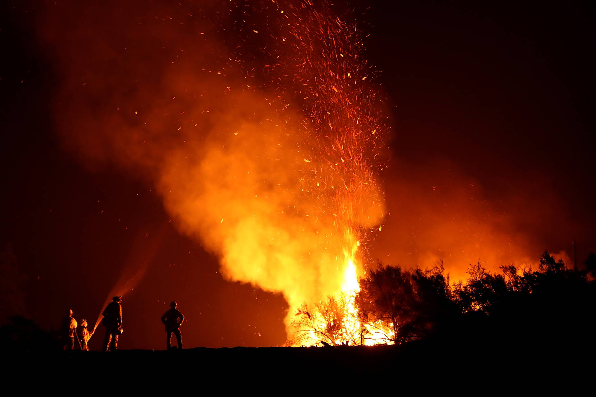 Cal Fire firefighters monitor a back fire as they battle the Medocino Complex fire on August 7, 2018 near Lodoga, California.     Justin Sullivan/Getty Images