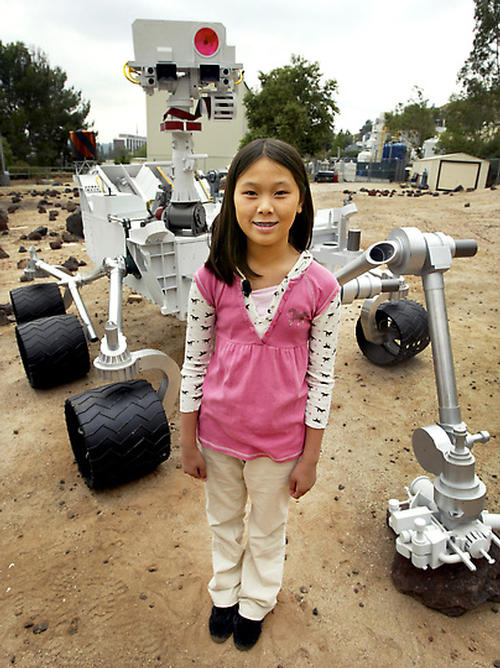 Clara Ma, winner of the essay contest to name the Mars Science Laboratory, Curiosity, poses before a model of the rover.