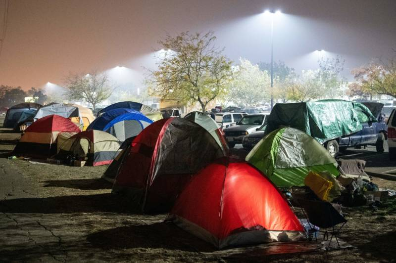 Evacuees rest in their tents for the night in a Walmart parking lot in Chico, California on November 17, 2018. Nearly 700 people remain listed as missing in the worst-ever wildfire to hit the state.