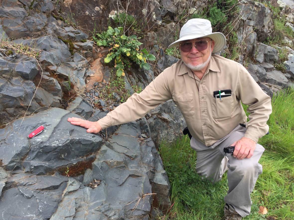 Eldridge Moores in one of the road cuts where rocks reveal the origins of the Sierra Nevada. (Craig Miller/KQED)