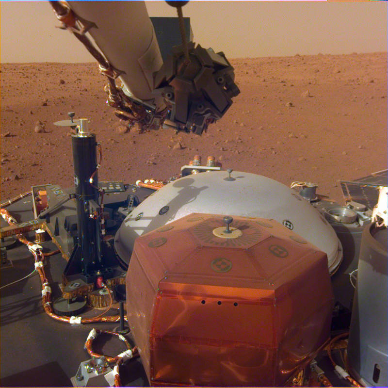 Image of Insight's top deck taken from the Instrument Deployment Camera on the lander's robotic arm. The copper colored object in the foreground is SEIS, Insight's seismometer, which will be placed on the ground to listen for Marsquakes. The gray dome behind SEIS is the wind shield that will be placed on top of it. The black cylinder on the left is HP3, the ground-boring thermal probe that will measure heat flow from within Mars.