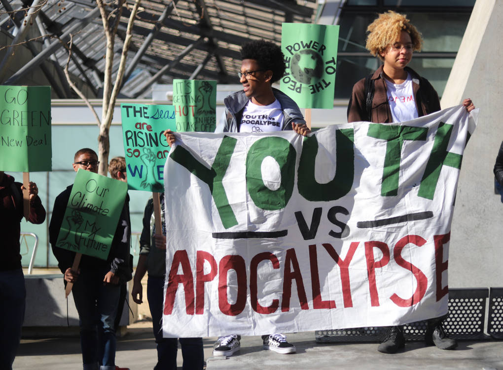 "Students Bruck and Jai hold up a banner that says ""Youth vs Apocalypse"" outside of the office building of Nancy Pelosi in downtown San Francisco on Friday March 15, 2019. (Lindsey Moore/KQED)"
