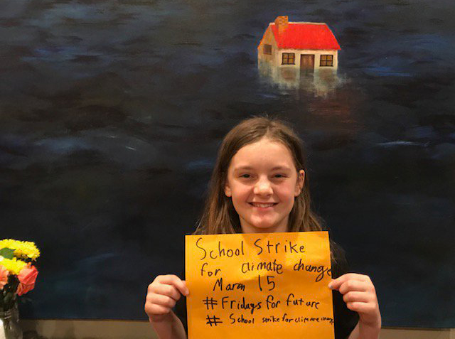 Fifth grade climate activist holding sign.