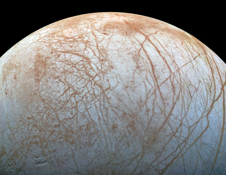 Jupiter's moon Europa, as photographed by the Galileo spacecraft. The pattern of cracks in the icy crust indicates that it floats on an ocean of liquid water.