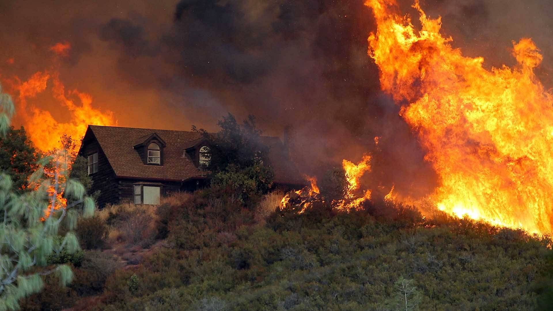 Flames from the Rocky Fire approach a house in Lower Lake, California, in 2015.  Justin Sullivan/Getty Images