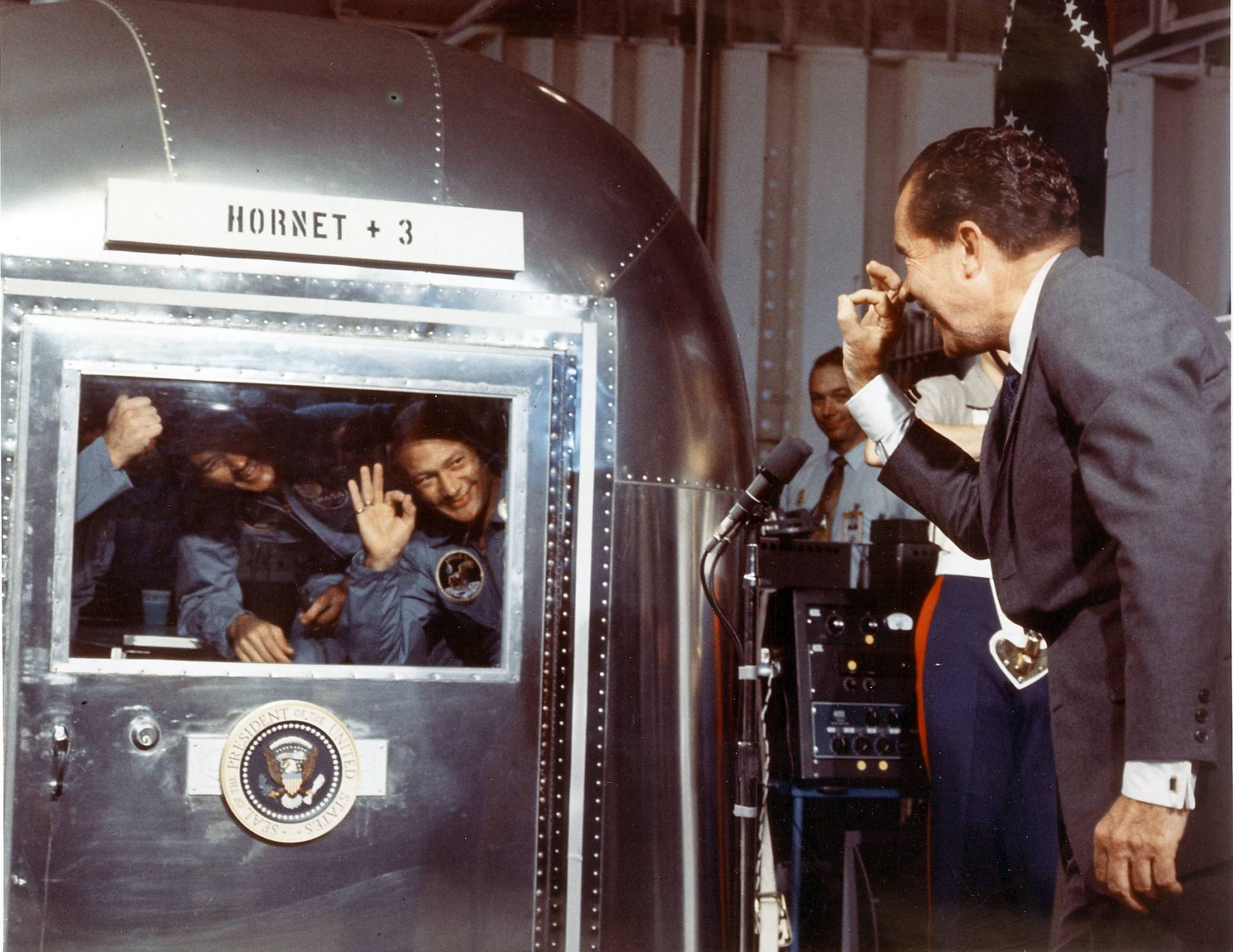 "President Richard M. Nixon and the Apollo 11 astronauts exchange ""A-OK signs"" through the window of the Mobile Quarantine Facility 24 July 1969 aboard the USS Hornet.  NASA/AFP/Getty Images"