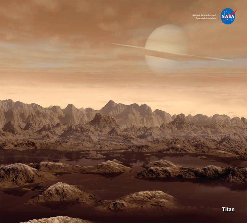 Artist concept of the surface of Titan, its high and rugged mountains, surface liquid methane, atmosphere, and Saturn in the hazy sky above.