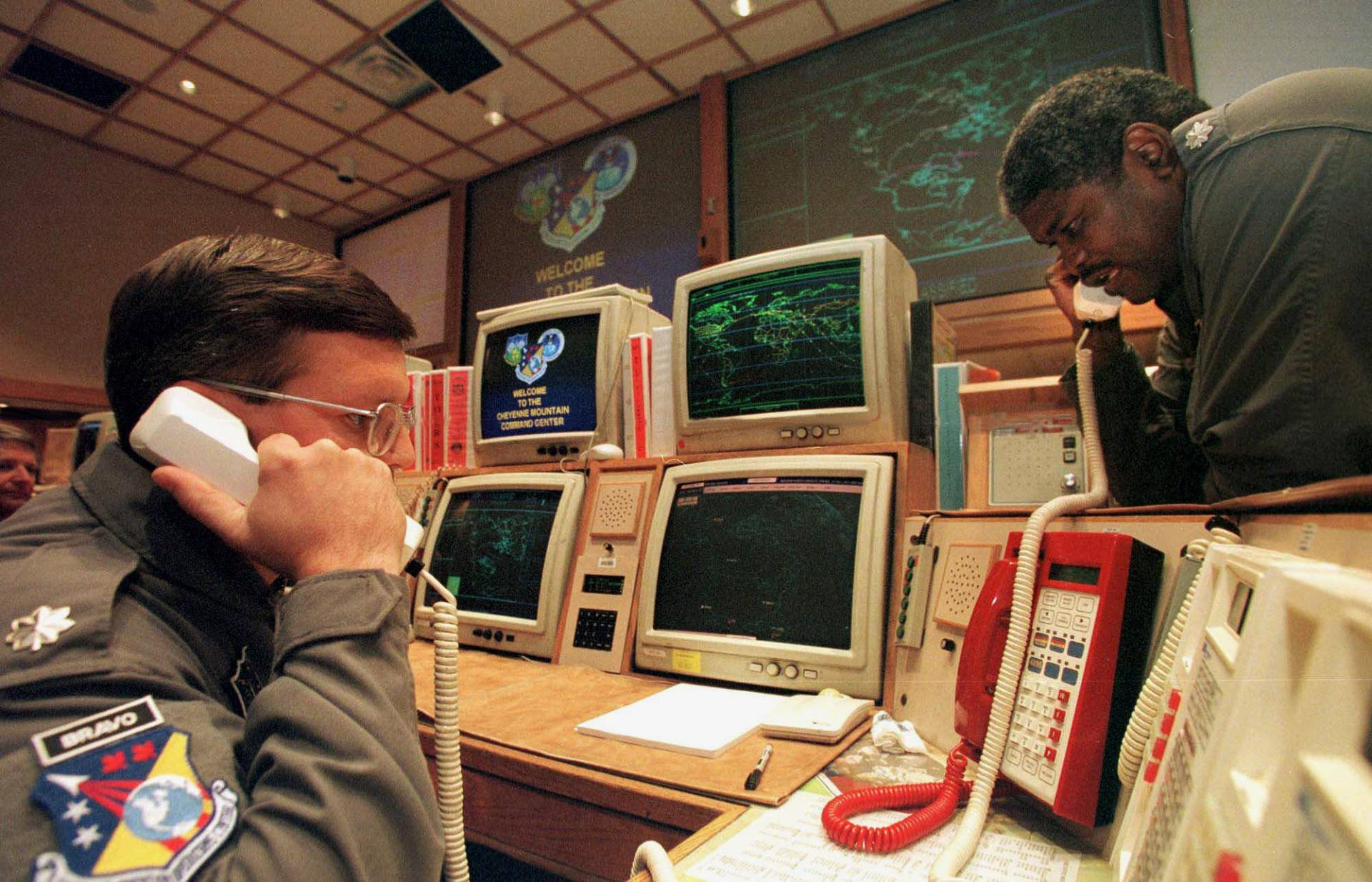 Missile Commanders confirm a launch warning over the phone during a practice drill at the North America Aerospace Defense Command, Nov. 9, 1999.  At the time, there were worries over whether the Y2K bug would render the complex missile tracking system inoperational after computers switched to the new year.  MARK LEFFINGWELL/AFP via Getty Images