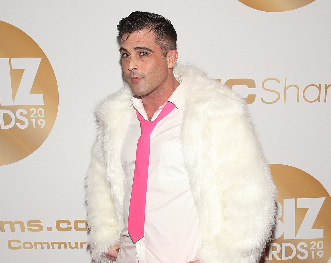 Lance Hart, an adult film performer who also runs two production companies poses in a white shirt, pink tie, and white furry coat at the 2019 XBiz Awards in Los Angeles.