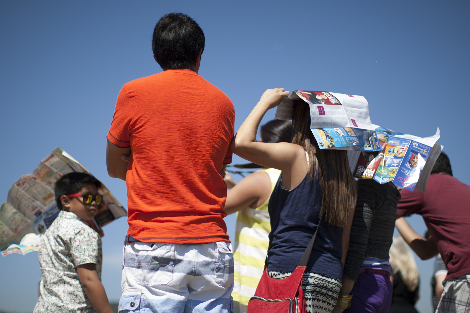People hold Hollywood tourist maps over their heads as makeshift sunshade in Griffith Park in March 2015 in Los Angeles, California. A record-breaking series of unusual heat waves made this the first March to have had six days with highs in the 90s or above in Los Angeles since at least 1877 when record-keeping began.