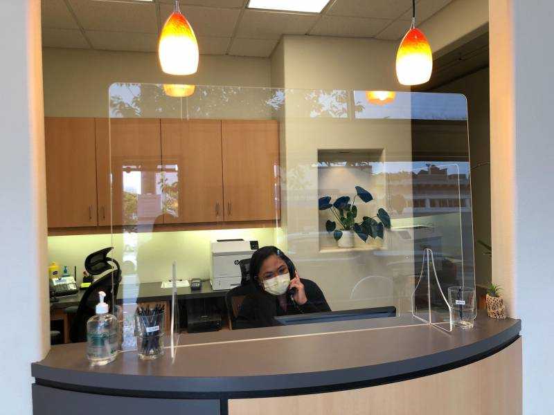 Office manager Cessalyn Maquinana at the front desk of the Better Living through Dentistry Office. New additions for the pandemic: plexiglass sneeze guards, separate cups for clean and used pens, and hand sanitizer.