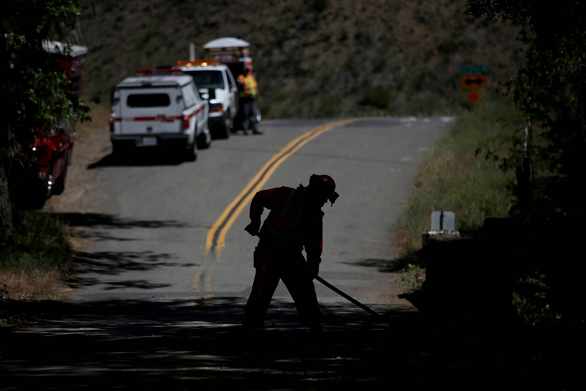 A fire crew sweeps the road to remove ground fuels and small trees along a road to help reduce the spread of fire in the event of a wildfire. Justin Sullivan/Getty Images