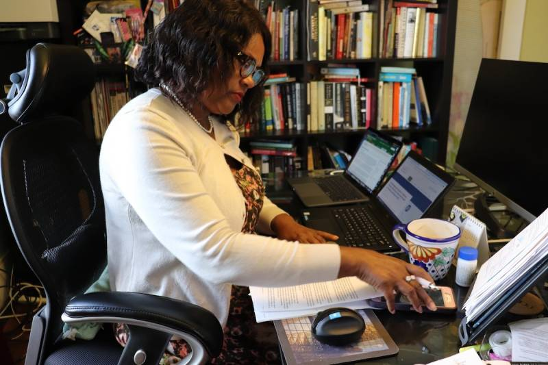 A woman with coffee skin and black hair, wearing a white sweater, sits at a desk in front of two laptops. This is Teron McGrew at her home office in North Oakland. Rows of books, with books stacked on top of them, fill her bookshelf.