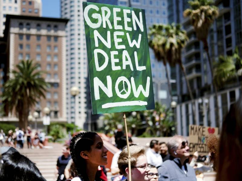 """Climate change activists holding signs join in on a rally supporting the """"Green New Deal"""" in Pershing Square in downtown Los Angeles on Friday, May 24, 2019."""