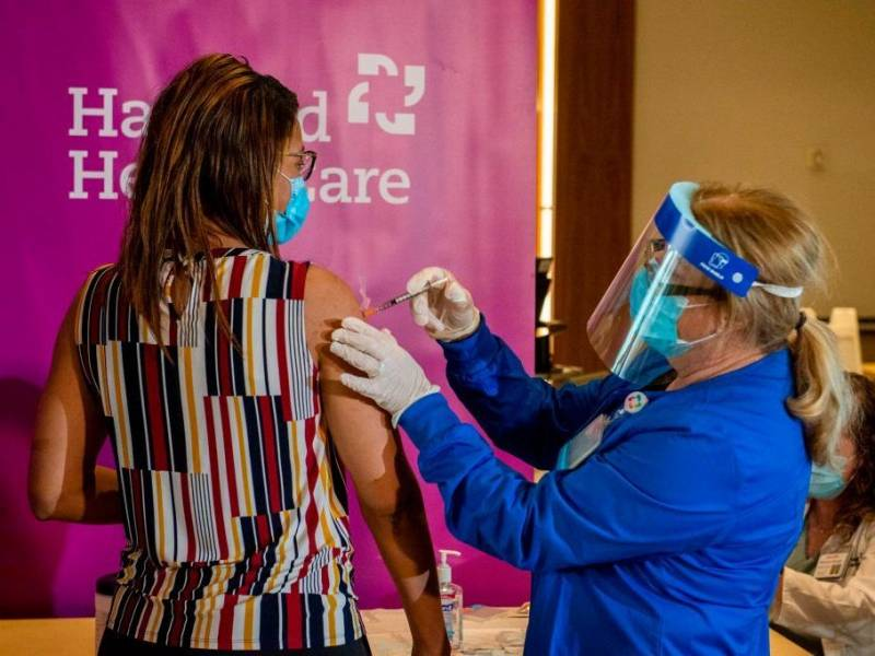 Dr. Melisha Cumberland is given the the second dose of the Pfizer/BioNTech vaccine in the arm by a medical worker wearing a face shield and a blue PPE suit.