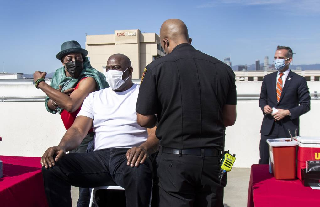 Arsenio Hall shows off his muscles to Magic Johnson before they both get a vaccine as Los Angeles Mayor Eric Garcetti looks on from the rooftop of parking structure at USC as a part of a vaccination awareness event at the university on March 24, 2021. Hall received the Johnson & Johnson vaccine. Johnson received the Pfizer-BioNTech vaccine.