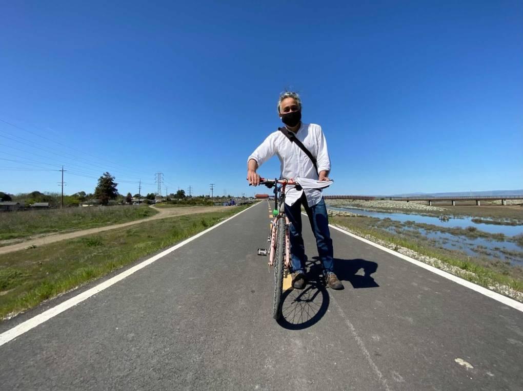 El alcalde del Este de Palo Alto, Carlos Romero, con su bicicleta en el nuevo dique que rodea partes de su ciudad. Las casas a la izquierda se encuentran a un extremo de la ciudad y a la derecha hay un arroyo que conduce a la bahía.