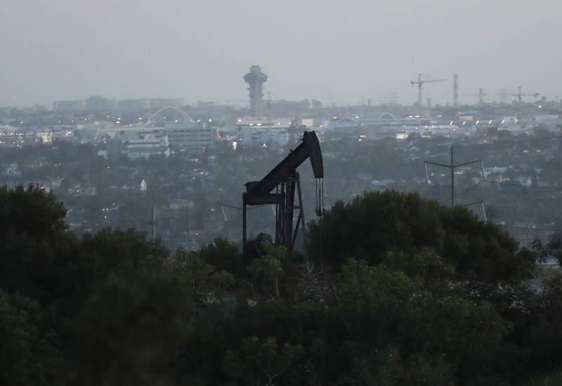 An oil rig with a city in the background.