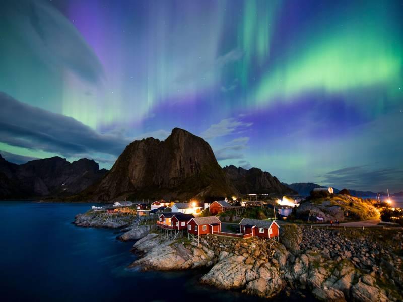Northern lights (aurora borealis) illuminate the sky over Reinfjorden in Reine, on Lofoten Islands, Arctic Circle, on September 8, 2017.